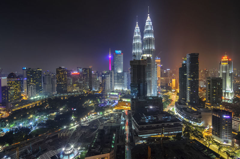 Illuminated petronas towers and city against clear sky at night
