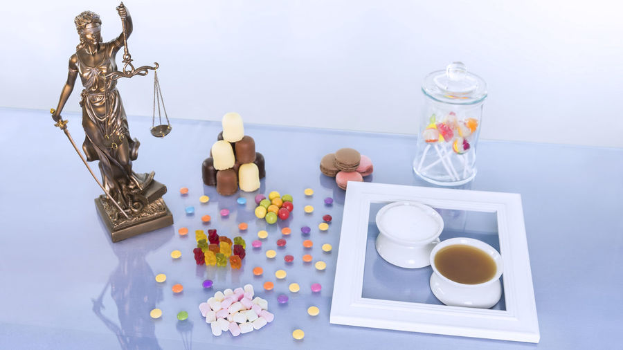 Justitia statue is on the table with many sweet foods. For comparison, there are each a bowl of sugar and a bowl of industrial sugar next to each other. Concept image. Fruit Gums Isoglucose Macarons Macaroons Marshmallow Statue Sugar Cheap Chocolate Beans Concept Corn Syrup Eu Food Food Food Industry Fructose Glucose Syrup Gummy Bears Justice Law Lollipops Overweight Sweets Unhealthy Eating Weight