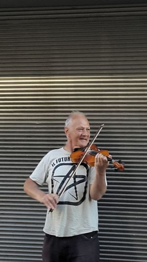 Mature Man Playing Violin While Standing Against Shutter