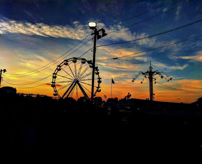 Silhouette ferris wheel against sky during sunset