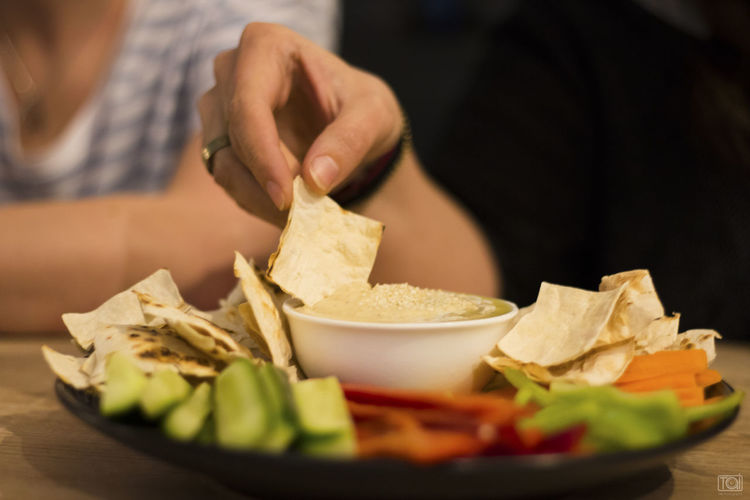 Close-up Food Food And Drink Freshness Hand Healthy Eating Human Body Part Human Hand Hummus Indoors  Mexican Food Midsection Nacho Chip One Person Preparation  Ready-to-eat Real People Selective Focus Snack Table Vegetable Wellbeing