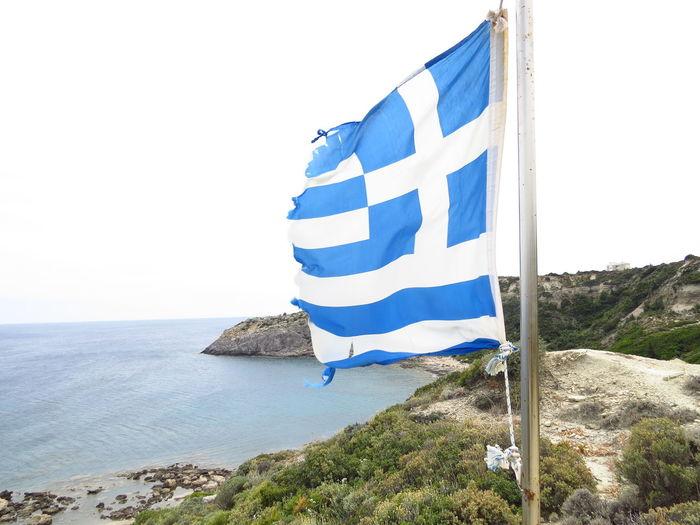 Greek flag waving by sea against clear sky
