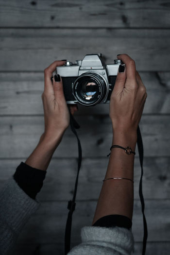 Midsection of woman photographing camera