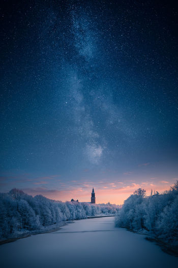 Frozen river and trees against star field