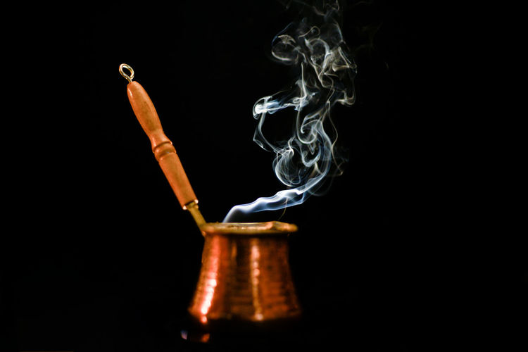 Close-Up Of Smoke From Traditional Coffee Cup Against Black Background