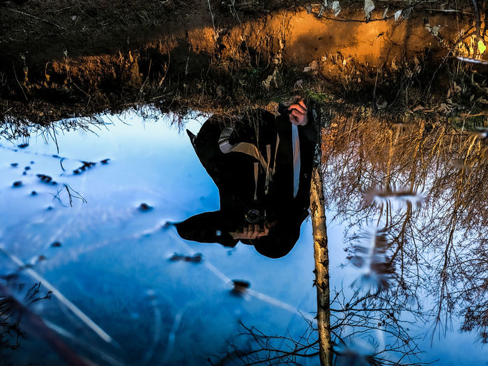 Reflection of man in puddle during winter