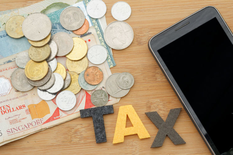 Tax concept Tax Smart Phone Internet Online  Payment Text Word Conceptual Concept Currency Coin Table Wireless Technology High Angle View Communication Close-up Money Paper Currency Wallet Savings