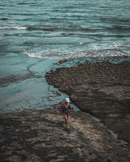 High angle view of woman standing on rock at beach