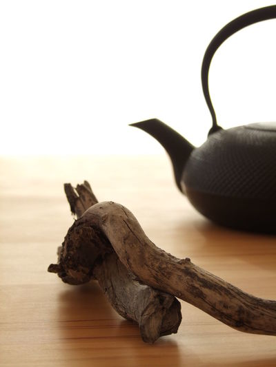 Close-up of wood and kettle on table