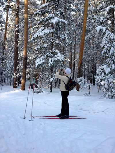 Full length of man skiing on snowy field against trees