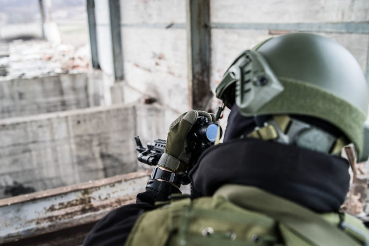 Close-up of army soldier aiming rifle while standing in building