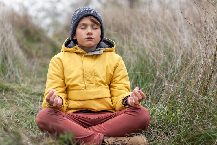 Small boy doing yoga relaxation exercises in lotus position during autumn day in tall grass.