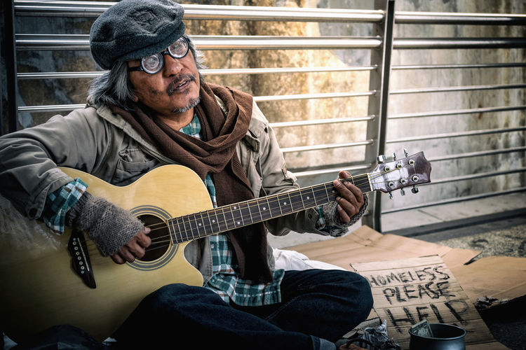 Portrait of homeless man playing guitar while sitting against railing