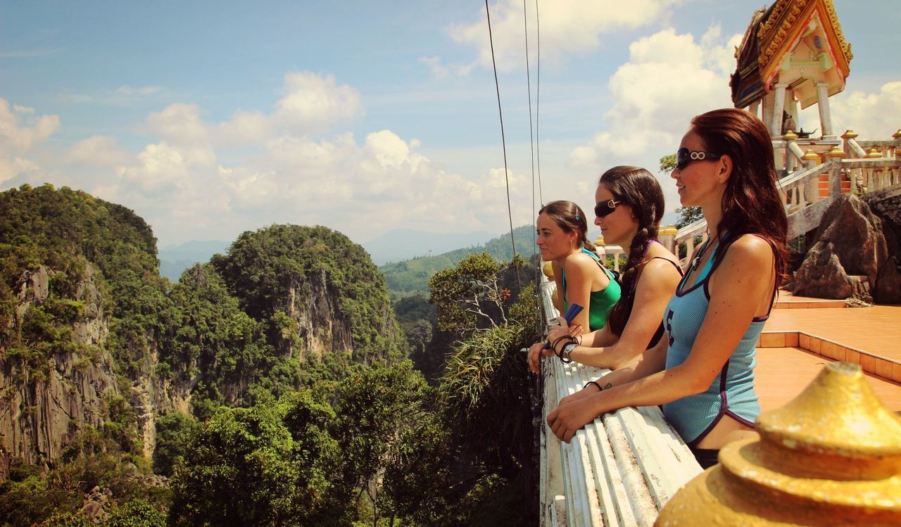 Friends Standing By Railing In Temple Viewing Mountains In Forest