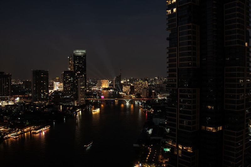 Top view cityscape of bangkok at night with lighting cruises on chao phraya river view