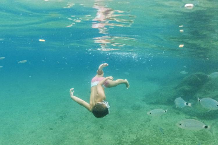 Full length of shirtless man swimming in sea