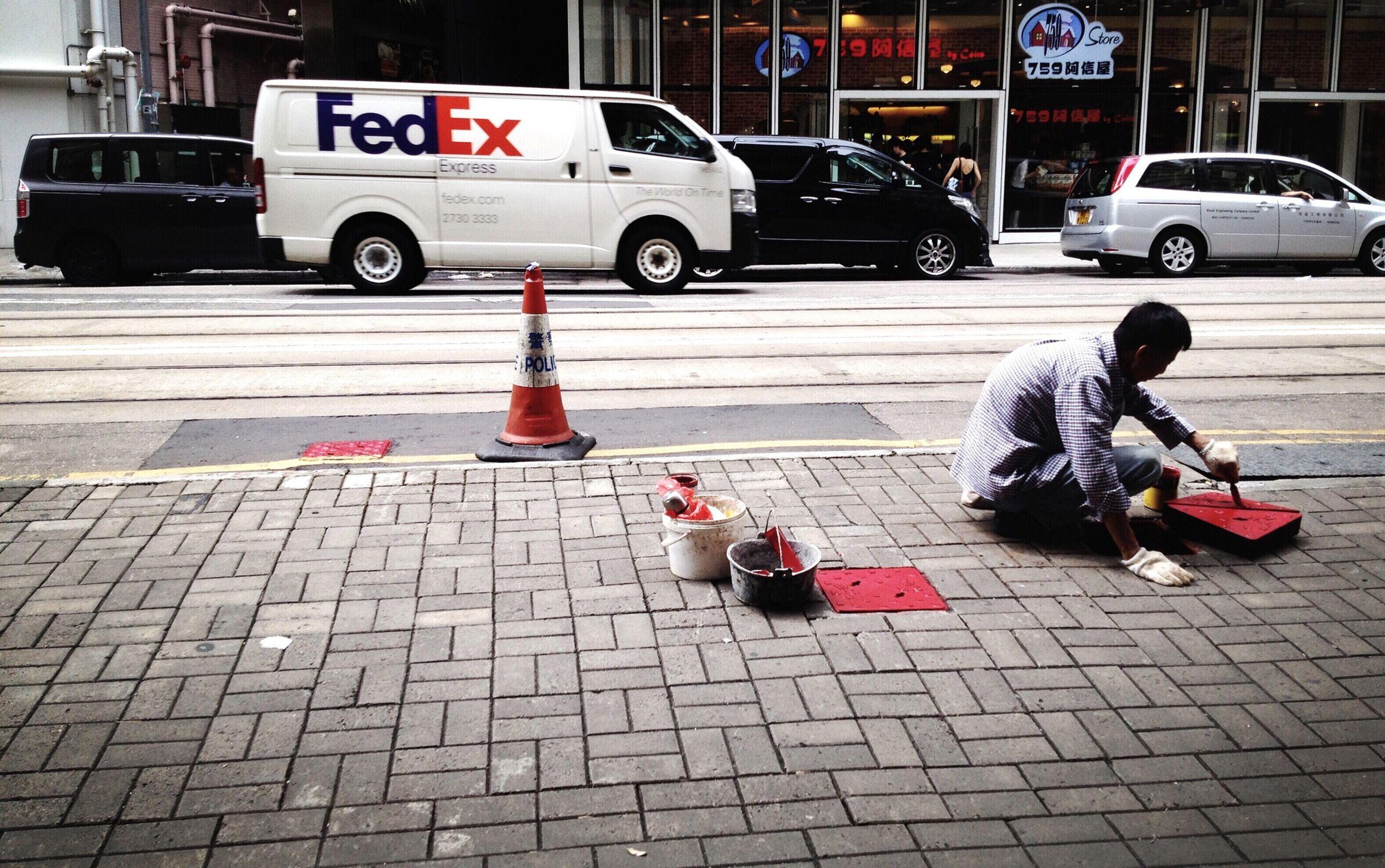 transportation, street, mode of transport, land vehicle, city, car, text, incidental people, sidewalk, building exterior, city life, communication, cobblestone, day, outdoors, guidance, men, city street, road