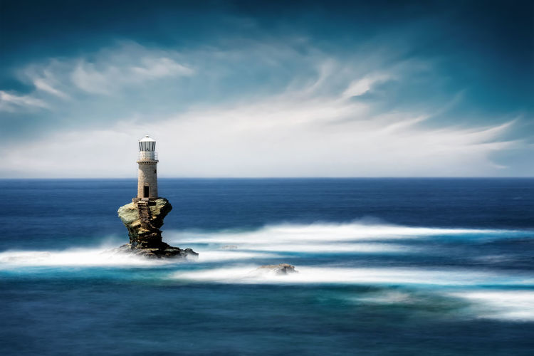 Scenic view of lighthouse in sea against sky