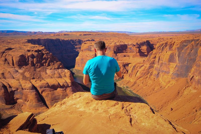 Rear view of man sitting on cliff at horseshoe bend
