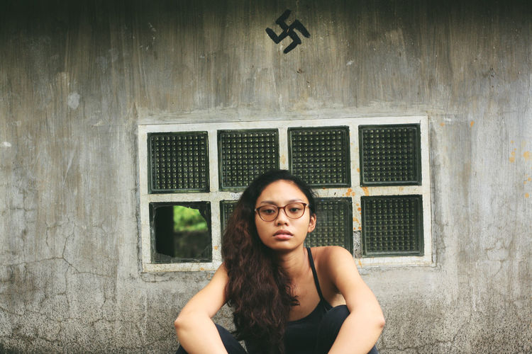 Portrait of young woman standing against wall