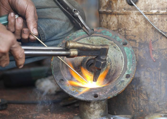 Welder Real People One Person Human Hand Working Human Body Part Men Blacksmith  One Man Only Motion Metal Industry Indoors  Holding Burning Making Metal Skill  Flame Heat - Temperature Occupation Workshop