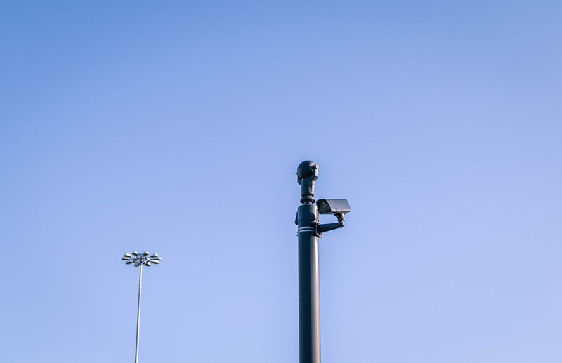 Low angle view of surveillance camera against clear blue sky