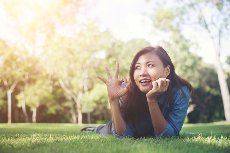 Happy young woman showing ok sign while lying on grass at park