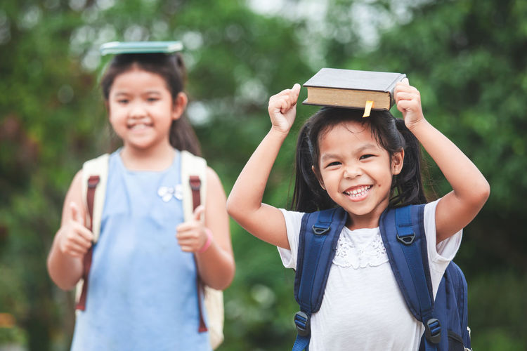 Back to school. Cute asian child girl with school bag and her sister put a book on head together with fun Asian  Fun Happy Reading Siblings Sister Student Writing Back To School Backpack Bag Child Cute Daughter Enjoy Friendship Girl Kid Knowledge Learn Pupil School Smiling Study Togetherness