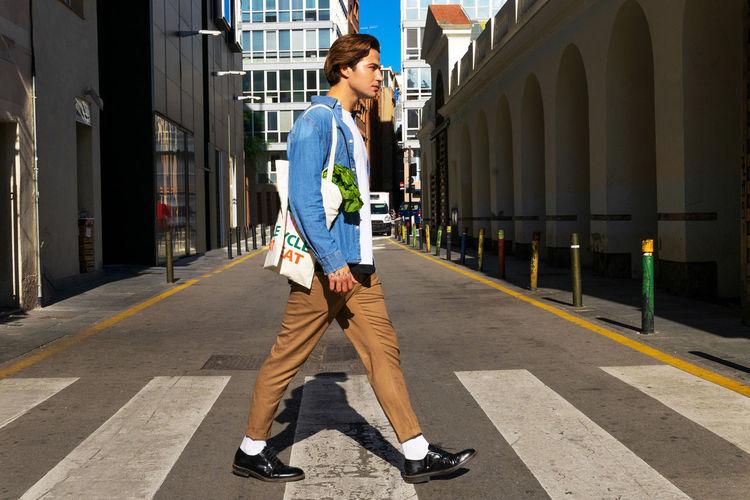Full length of man standing on street against buildings in city