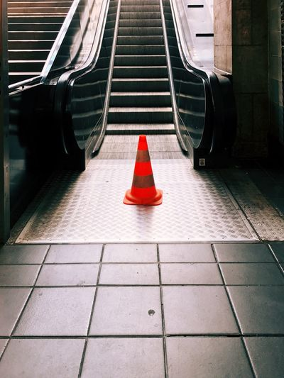 Traffic cone by escalator at subway station