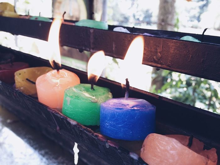 Close-Up Of Multi Colored Tea Light Candles On Railing