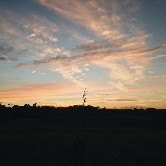 Silhouette of electricity pylon against dramatic sky