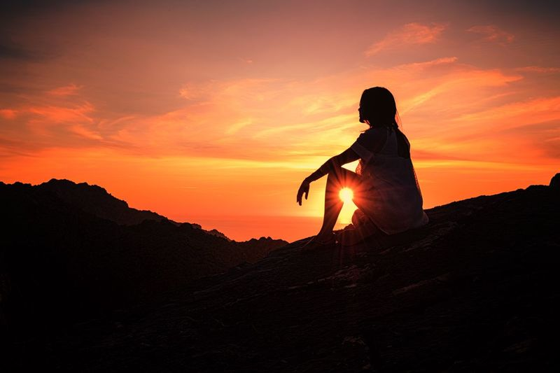 Silhouette Woman Sitting On Mountain Against Orange Sky