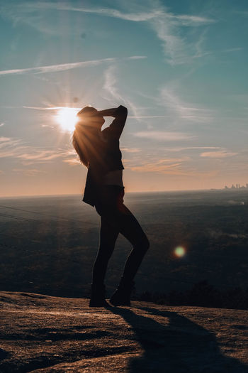 Man standing on sea shore against sunset sky