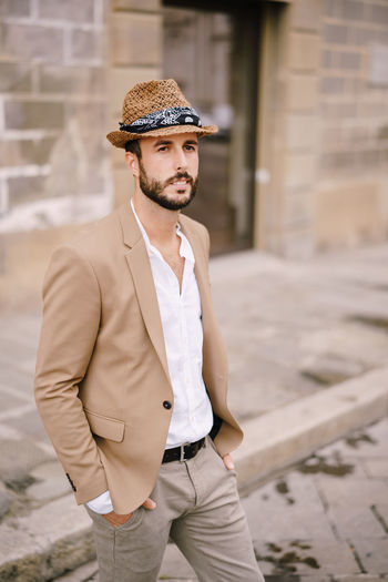 Man wearing hat looking away while standing outdoors