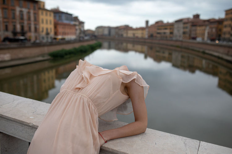 Woman bending over backwards on bridge in city