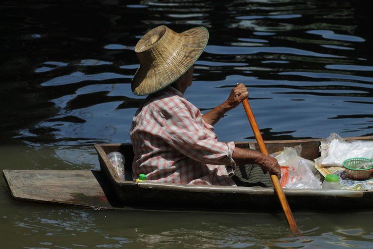Side view of man oaring boat in river