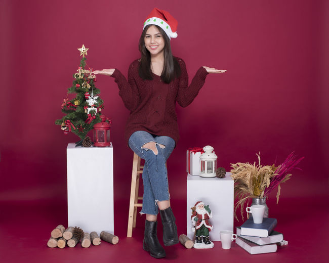 Portrait of woman gesturing amidst christmas decorations over red background