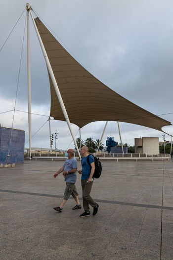 Men with umbrella on sidewalk against sky