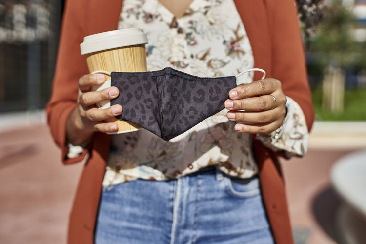 Midsection of woman holding ice cream standing outdoors