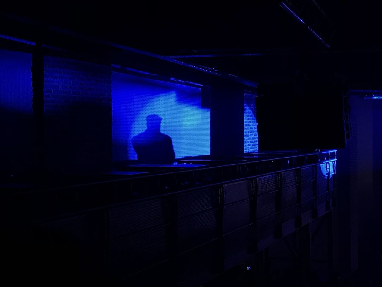 indoors, one person, real people, illuminated, window, dark, night, sitting, men, railing, architecture, silhouette, blue, rear view, built structure, lighting equipment, wall - building feature, lifestyles, nightlife, contemplation