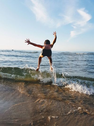 A summer day on the Baltic coast. a boy plays with the waves. Ocean Kidsphotography Kids Playing Kids Having Fun Jumping Water Wave Sea Beach Happiness Motion A New Beginning