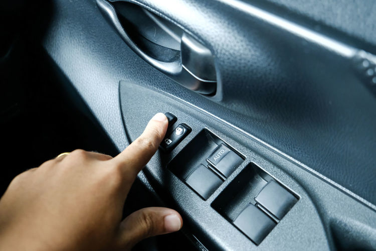 Close-up of hand pressing push button in car