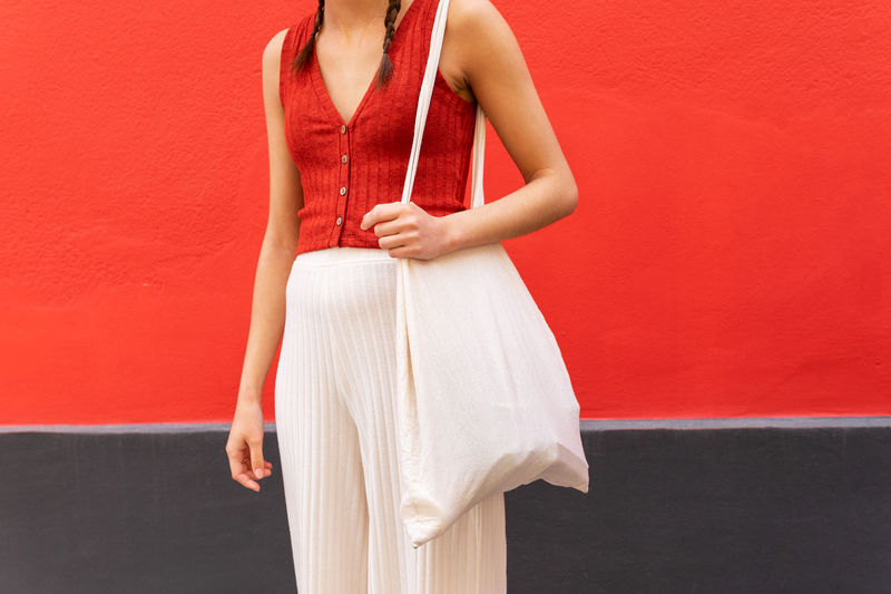 Midsection of woman standing against red wall