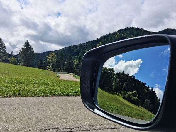 Side-view Mirror Sky Cloud - Sky Car Tree Transportation Reflection Mirror Road Trip Mode Of Transport Land Vehicle Road Green Color Day Vehicle Mirror Nature Window Landscape No People Mountain