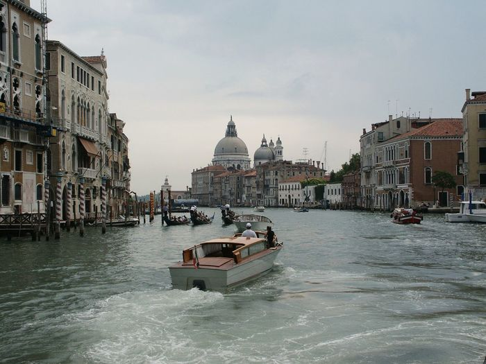 Boats moving on grand canal amidst buildings against sky