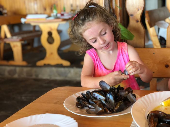 Girl Holding Seashell By Table At Restaurant