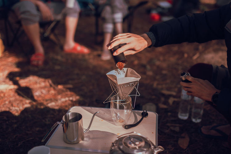 Close up photo of man preparing coffee at camping in forest.