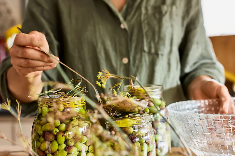 Woman prepares fermented olives in glass jars in the kitchen. autumn vegetables canning.