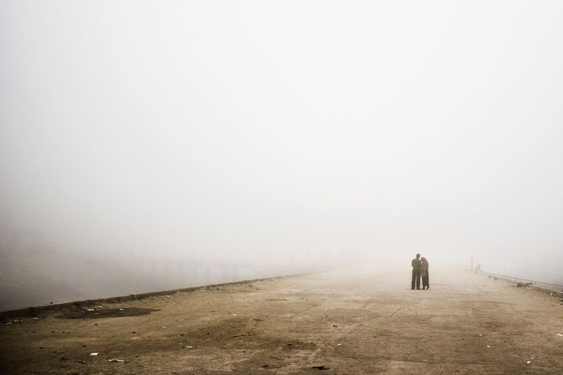 People At Standing On Road In Foggy Weather